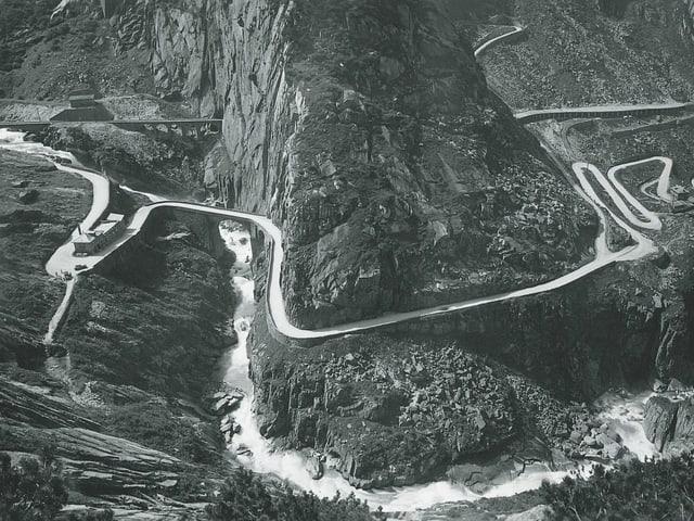 Historische Aufnahme der Schöllenenschlucht mit Serpentinenkurven und einer Eisenbahnbrücke.