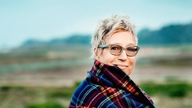 Eine blonde Frau mit Brille in der Natur.