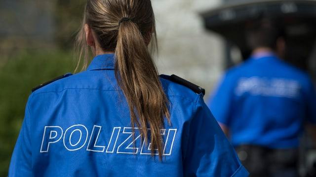 Aufnahme einer Rückansicht einer langhaarigen Polizistin