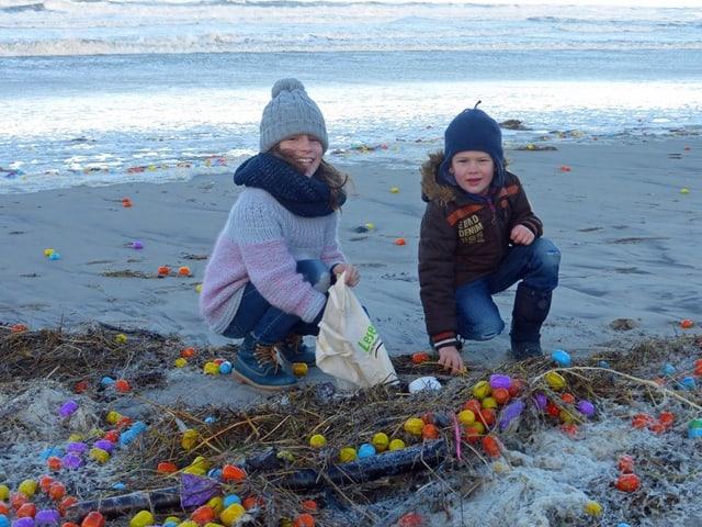 Kinder sammeln farbige Überraschungseier an Strand.