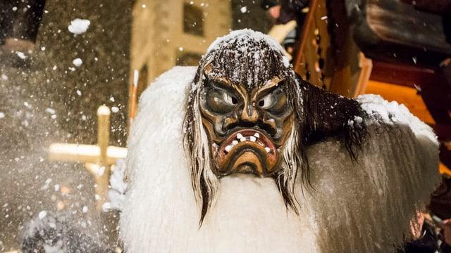 Eine Tschäggättä (Mensch in Maske und Kostüm) unterwegs im Lötschental