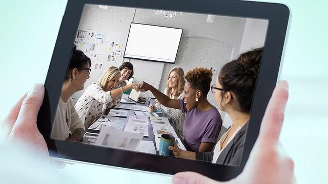 Tablet zeigt ein Bild mit Frauen, die sich mit der Faust anstossen.