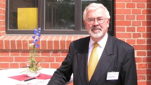 Der Autoexperte Helmut Becker posiert vor seinem Wirtschaftsinstitut in München