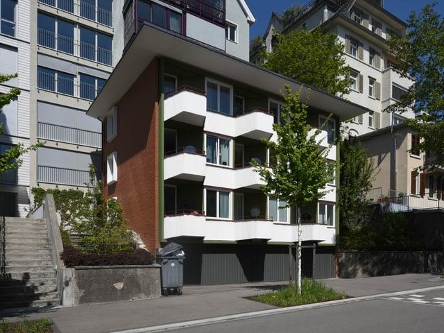 Ein Apartmenthaus mit weissen Balkonen.