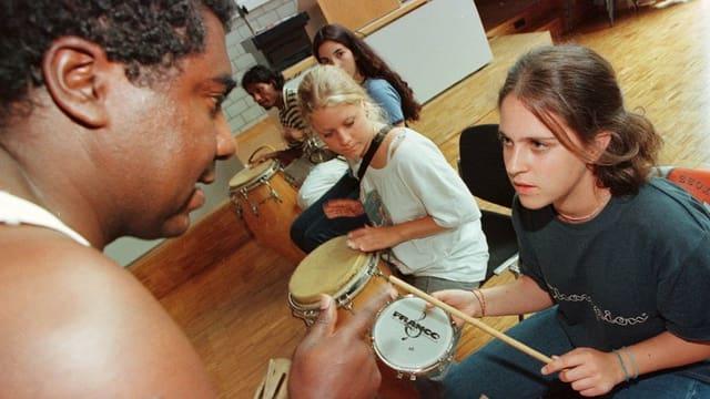 Ein schwarzer Lehrer bringt ein paar Mädchen das Bongo-Spielen bei.