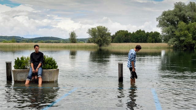 Zwei Männer stehen im Hochwasser beim Hafen in Gottlieben (TG) am 19. Juni 2016. (keystone)