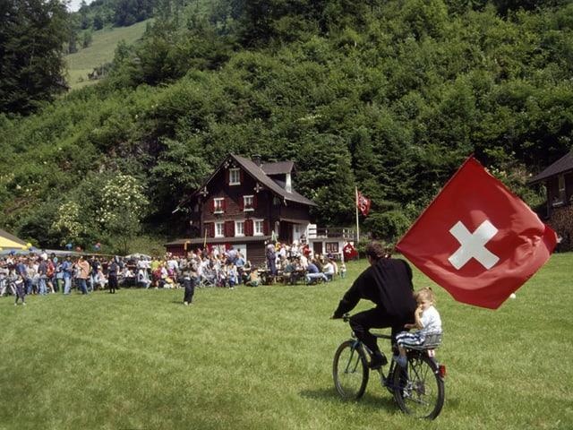 Mann auf Fahrrad mit Schweizer Fahne und Kind auf Gepäckträger.