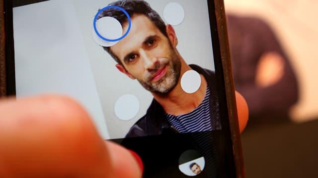 Das Porträit eines Mannes auf einem Handybildschirm.