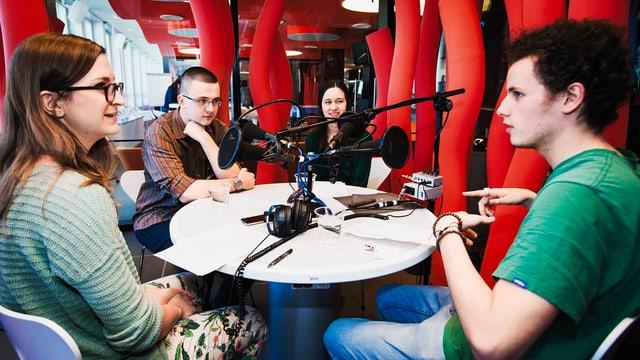 Vier Menschen sind an einem Tisch vor Mikrofonen ins Gespräch vertieft.