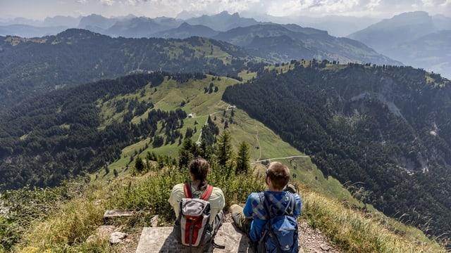 Zwei Wanderer sitzen auf Aussichtspunkt