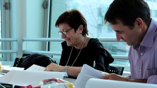 Anna-Alice Dazzi e Gian Michael da la giuria dal Pled rumantsch 2016. Els guardan sin fegls e sesan vid ina maisa da biro.