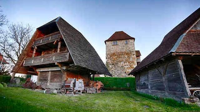 Zwei Holzspeicher, dazwischen im Hintergrund ein Burgturm aus Stein gebaut.