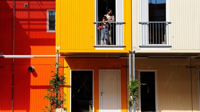 Sechs orange, gelbe und weisse Container mit Wohnungen für Asylbewerber. Oben in der Mitte schauen zwei dunkelhäutige Menschen aus dem Fenster.
