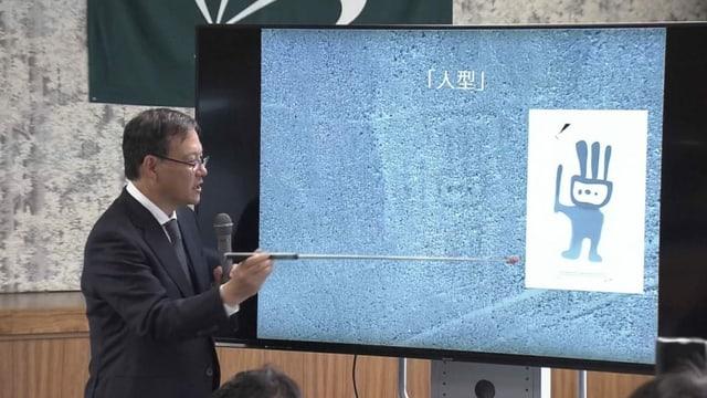 Japanischer Forscher zeigt auf einer Leinwand die vermeintliche Figur.
