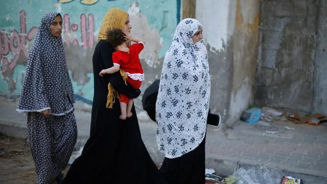 Drei palästinensiche Frauen mit einem Kleinkind verlassen ihr Haus