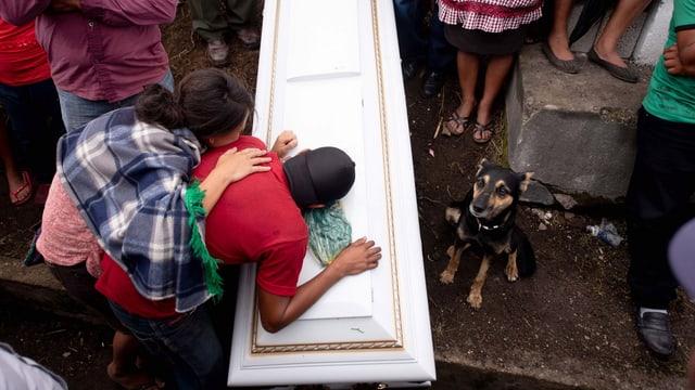 Trauernde Menschen neben Sarg