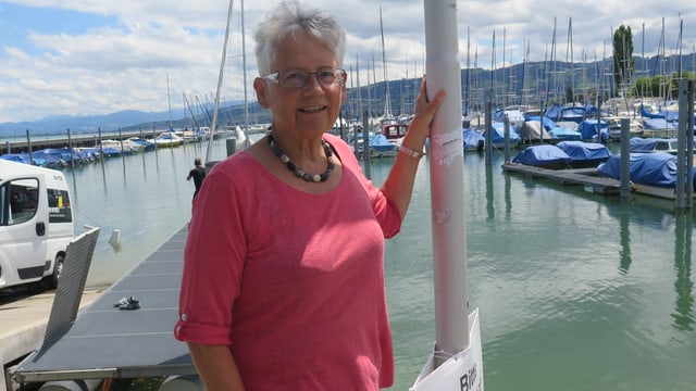 Frau steht am Seeufer, im Hintergrund ein Hafen.