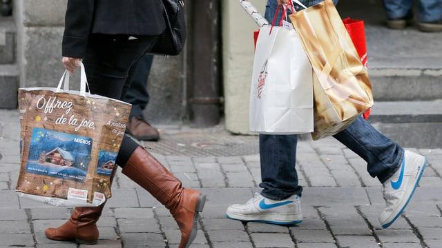 Ein Mann und eine Frau tragen Einkaufstüten