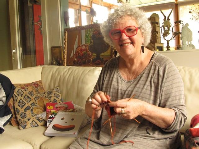 Madame Tricot sitz auf ihrem Ledersofa in der Stube und strickt.