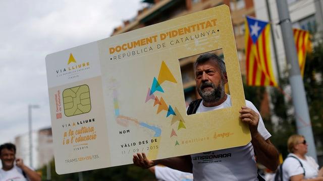 Ein Mann posiert mit einer Identitätskarte von Katalonien.