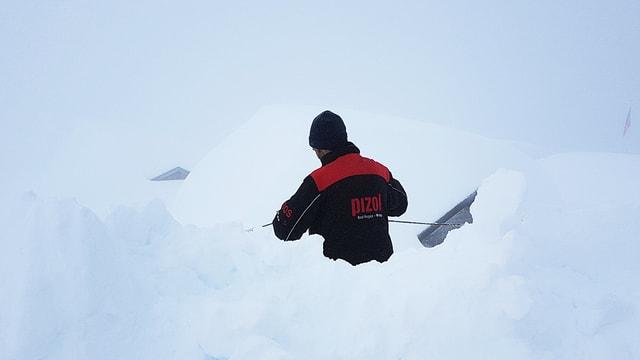 Mann steht bis zur Hüfte im Schnee
