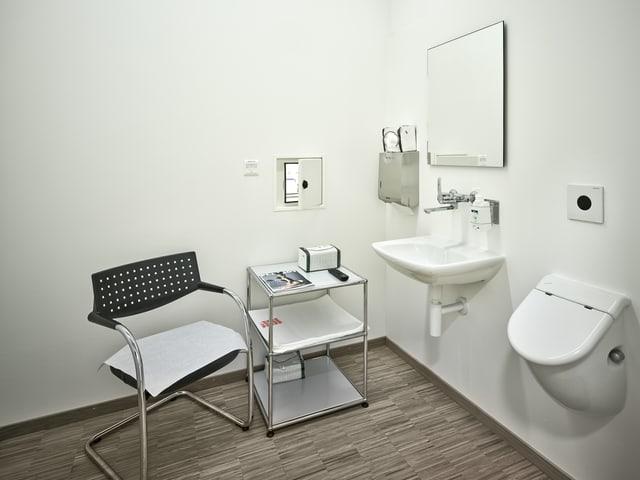 Eins steril weisser Raum mit Stuhl, Lavabo und einer Art Pissoir an der Wand.