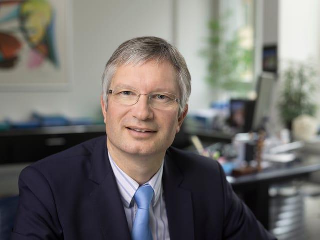 Mann mit blauer Krawatte und Brille