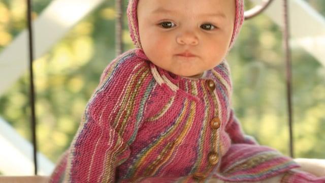 Baby mit gestrickter Mütze und gestricktem Jäckchen