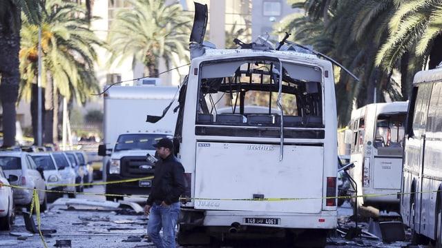 Ein Mann steht vor dem zerstörten Bus in Tunis.