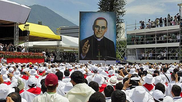 Ein grosses Porträt von Romero über einer Menschenmenge auf einem Platz.