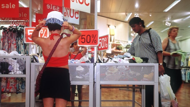 Kunden in der Kleiderabteilung eines Warenhauses  an Wühltischen mit Schilden «50 Prozent»