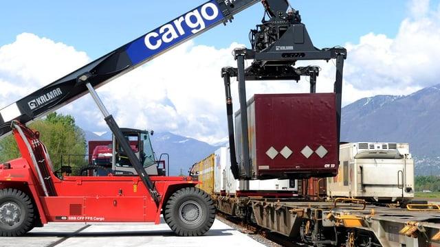 Ein Kranwagen lädt einen Container auf einen Bahnwagen.