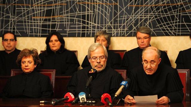 Sitzende Richter in schwarzen Roben, im Vordergrund stehen Mikrofone.