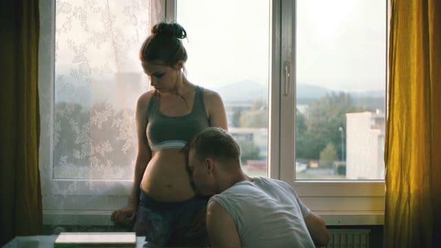 Eine schwangere junge Frau mit nacktem Bauch. Ein junger Mann hält sein Gesicht an den Bauch.