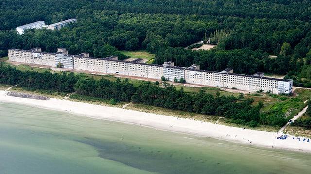 Blick auf einen langen Bau an der Meeresküste.