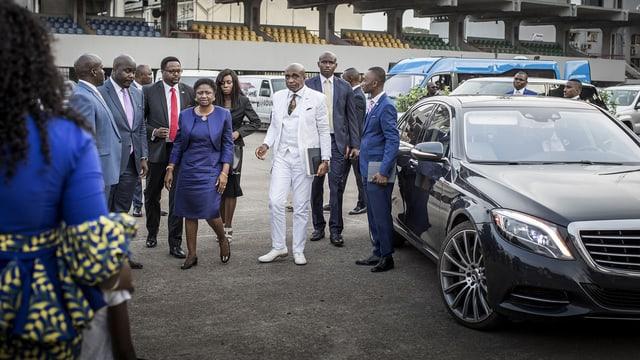 Oberhäupter einer Pfingstgemeinde neben Autos.
