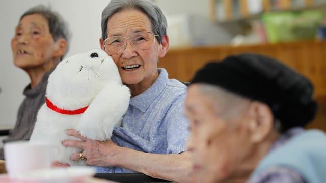 Eine japanische alte Frau hält ein Robbenstofftier in den Armen und lächelt.