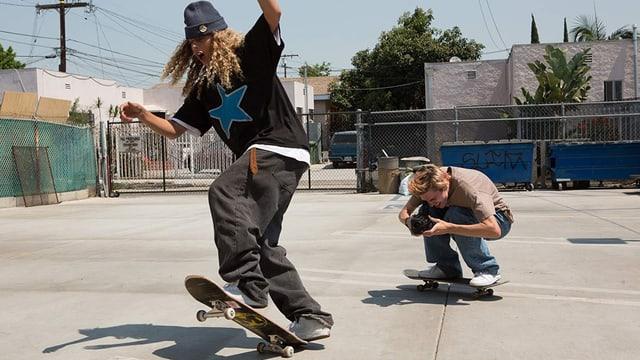 Ein Junge auf dem Board filmt mit der VHS-Kamera seinen Freund, der einen Skater-Trick vorführt.