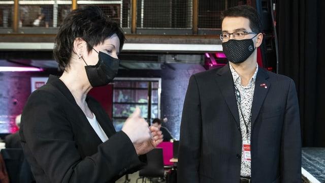 Frau und Mann, beide mit Schutzmasken