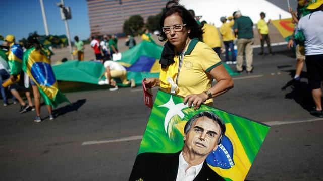 Frau in gelb-grünem Fussballtrikot der  Seleção mit einem gemalten Porträt-Bild Bolsonaros, dahinter weitere Menschen in Fussballshirts.