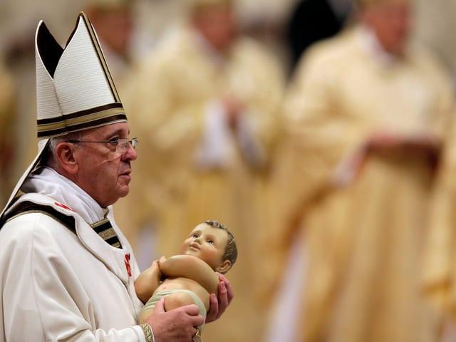 Der Papst trägt eine Jesus-Puppe.