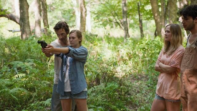 Menschen stehen im Wald und eine Frau macht Schiessübungen mit einem Revolver.