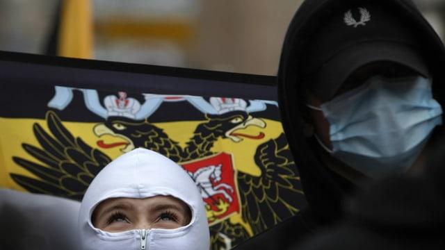Maskierte russische Nationalisten, Fahne im Hintergrund