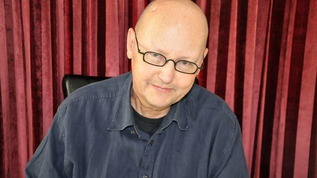 Porträtbild von Claude Cueni vor einem roten Vorhang.