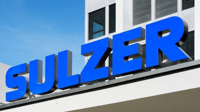 """Blaue Buchstaben formen den Schriftzug """"Sulzer"""" auf einem Vordach eines Firmengebäudes."""