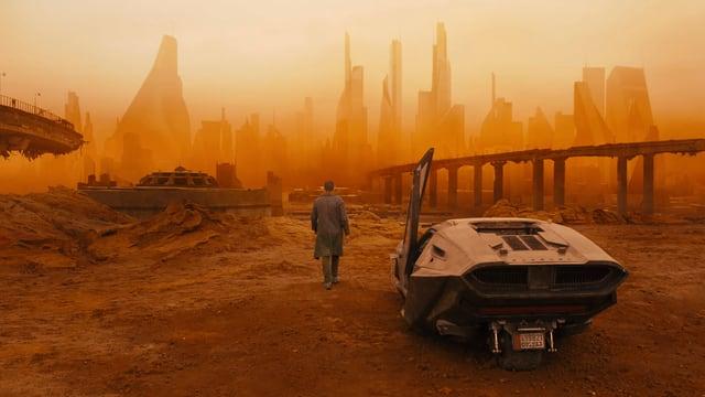 Ein Auto steht in einer leeren und öden Umgebung, im Hintergrund sieht man die Skyline von Los Angeles.