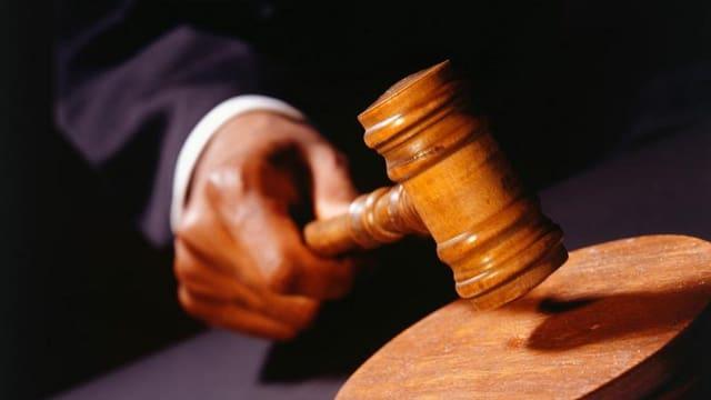 Ein Richter schlägt mit einem Hammer auf eine Holzplatte