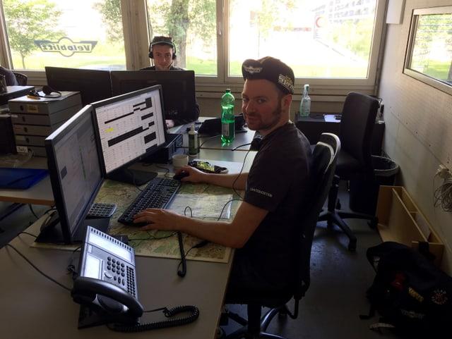 Zwei Männer sitzen am Computer und koordinieren die Einsätze der Fahrer.