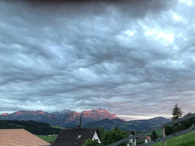 Dunkelgrauer Himmel. Die Wolkendecke ist aufgewühlt und erinnert an die Meeresoberfläche bei Sturm.