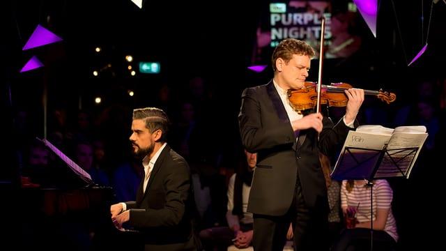 Ein Mann spielt Violine auf der Bühne, daneben ein weiterer Piano.